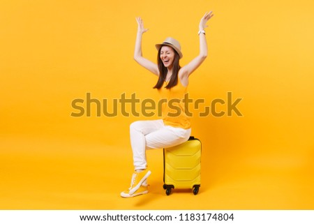 Traveler tourist woman in summer casual clothes, hat sit on suitcase isolated on yellow orange background. Female passenger traveling abroad to travel on weekends getaway. Air flight journey concept #1183174804