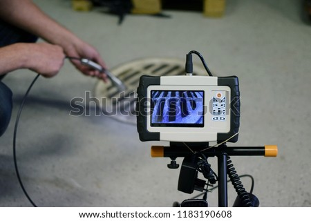 Man start using sewer inspection camera. Monitor showing picture from camera head that inspector is holding. #1183190608