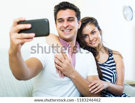 Positive young spouses posing and making selfie on smartphone. Focus on the man #1183246462