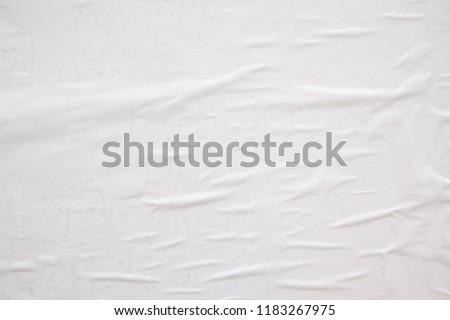 peeling white wrinkled street poster glued to a billboard wall #1183267975