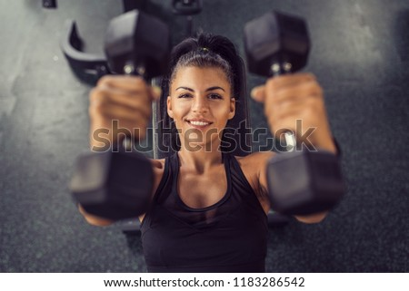 Concentrated woman lifting dumbbells in gym