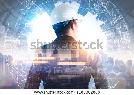 The double exposure image of the engineer standing back during sunrise overlay with cityscape image and futuristic hologram. The concept of engineering, construction, city life and future. #1183302868