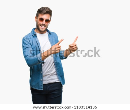 Young handsome man wearing sunglasses over isolated background smiling and looking at the camera pointing with two hands and fingers to the side. #1183314136