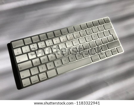 Computer keyboard. Isolated on the gray background. White keyboard with silver basis