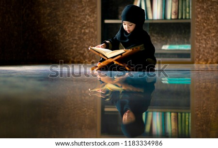 Asian Indonesian Muslim kid is reading the Quran. The Quran is indicated as the guided book for all Muslim and it is direction  to be on the heaven of God.Mosque,Islam,religion and knowledge concept. #1183334986