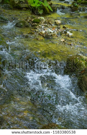 A small mountainriver flowing through the mountain valley in Low Tatra region. Hiking trail along the mountain stream. Tatra mountains in Slovakia, Europe. #1183380538