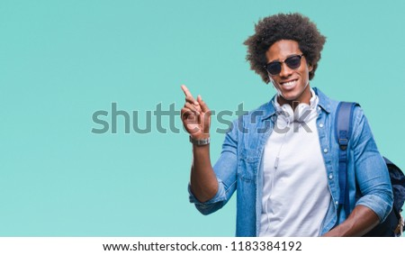 Afro american man wearing headphones and backpack over isolated background very happy pointing with hand and finger to the side #1183384192