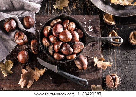 Roasted chestnuts served in a special perforated chestnut pan on an old wooden table #1183420387