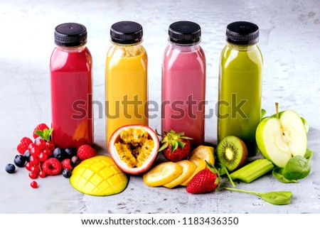 Flat-lay of colorful smoothies in bottles with fresh tropical fruit and superfoods on concrete background #1183436350