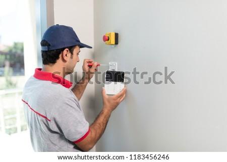 Man installing security alarm system #1183456246