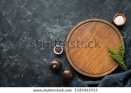 Spices, Herbs, Cutting board for cooking. Round wooden cutting board on black concrete backdrop. Top view with copy space for text. Menu, recipe mock up, banner background #1183461955