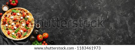 Italian pizza and pizza cooking ingredients on black concrete background. Tomatoes on vine, mozzarella, black olives, herbs and spices. Copy space for text. Banner composition #1183461973
