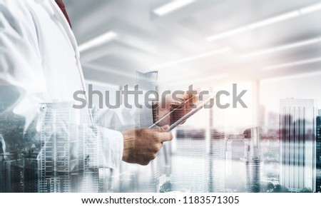 Double exposure of confident doctor in white sterile coat standing inside hospital office and modern cityscape view on background. Concept of modern medical industry #1183571305