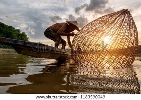 Fishermen fishing in the early morning golden light,fisherman fishing in Mekong River ,Thailand,Vietnam,myanmar,Laos #1183590049