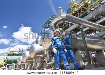 group of industrial workers in a refinery - oil processing equipment and machinery  #1183609642