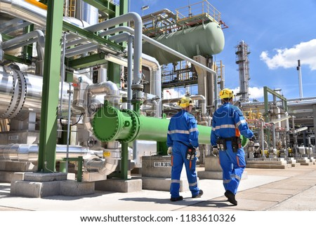 chemical industry plant - workers in work clothes in a refinery with pipes and machinery  #1183610326