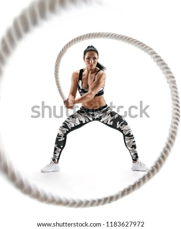 Woman doing exercises with battle rope. Photo of muscular model in military sportswear isolated on white background. Strength and motivation #1183627972