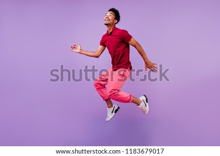 Funny guy in red t-shirt jumping and looking up. Studio portrait of emotional african male model posing on purple background. #1183679017
