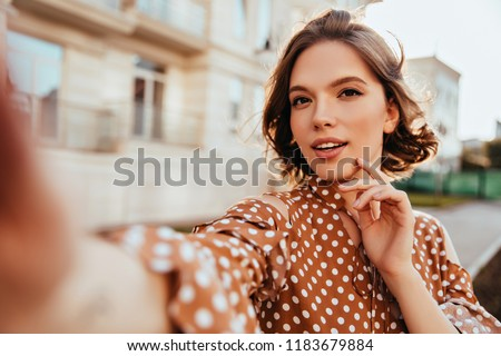 Interested glamorous woman in brown attire making selfie. Magnificent brunette girl taking picture of herself while walking around town. #1183679884