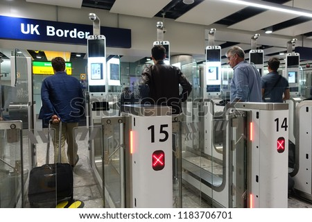 London, UK - July 29, 2018: Air travellers pass through automated passport border control gates at Heathrow Airport. The UK Border Force is on a recruitment drive in gearing up for Brexit. #1183706701
