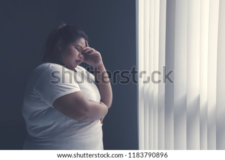 Picture of stressed fat woman having headache while standing by the window
