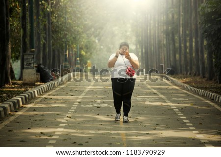 Picture of fat woman holding a mobile phone while walking on the road