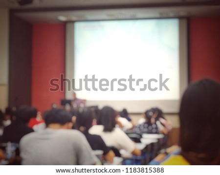 Blurred image of examination room with students sitting on lecture chair to study hastily especially for an examination via speaker show in display projector screen in university. Education concept. #1183815388