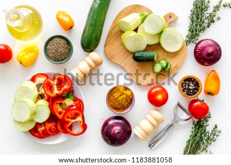 Cooking vegetable stew concept. Fresh vegetables squash, bell pepper, tomato, spices and cutting doard on white background top view #1183881058