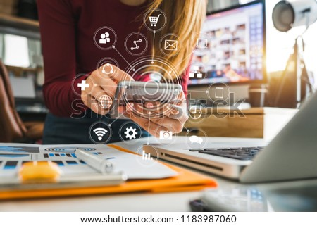 Digital marketing media in virtual screen.businesswoman hand working with mobile phone and modern compute with VR icon diagram at office in morning light   #1183987060