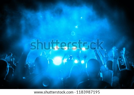 Silhouettes of concert crowd in front of bright stage lights #1183987195