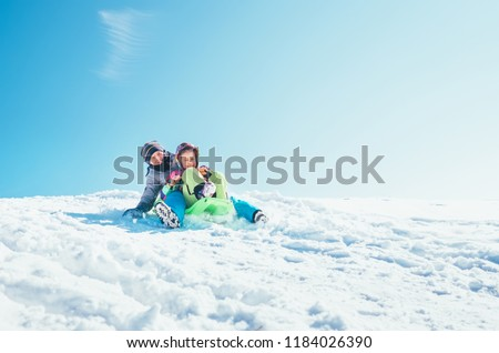 Brother and sister slide down from the snow slope sitting in one slide. Enjoying the winter sledding time  #1184026390