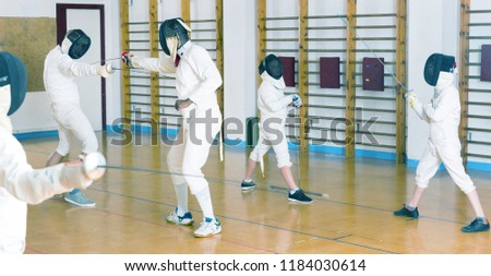 Adults and teens wearing fencing uniform practicing with a foil at a gym #1184030614