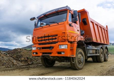 Sverdlovsk Oblast, Russia - July 20, 2018: dump truck rides on the mountain road under construction #1184062024