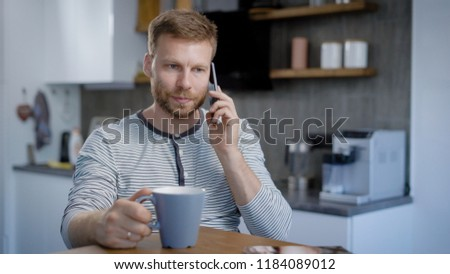 A man is sitting in his kitchen, and talking on the phone. Breakfast, coffee and a pleasant time for conversation with friends. Modern lifestyle #1184089012