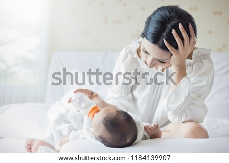 portrait of Asian mother nursery feeding bottle of formula milk to newborn baby in bed suffering from post natal depression. Health care single mom motherhood stressful concept. Royalty-Free Stock Photo #1184139907