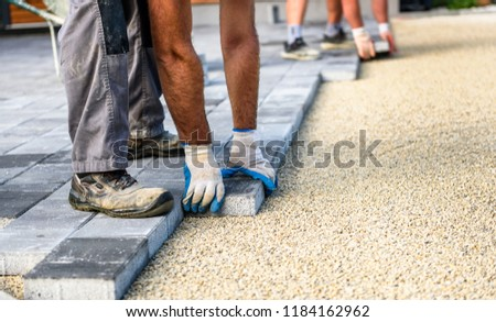 Laying gray concrete paving slabs in house courtyard driveway patio. Professional workers bricklayers are installing new tiles or slabs for driveway, sidewalk or patio on leveled sand foundation base. #1184162962