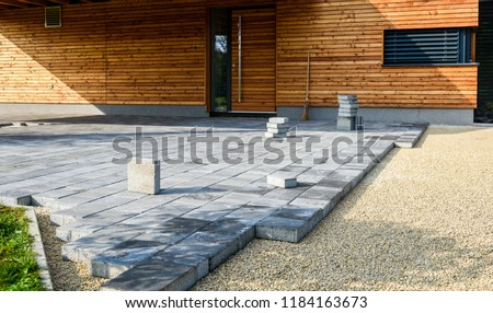 Laying gray concrete paving slabs in house courtyard driveway patio. Professional workers bricklayers are installing new tiles or slabs for driveway, sidewalk or patio on leveled sand foundation base. #1184163673