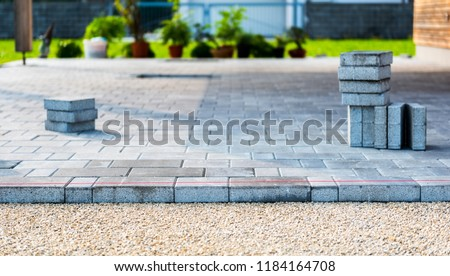 Laying gray concrete paving slabs in house courtyard driveway patio. Professional workers bricklayers are installing new tiles or slabs for driveway, sidewalk or patio on leveled sand foundation base. #1184164708