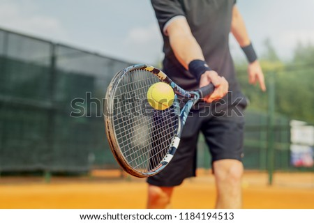 Close up of man playing tennis and beating the ball with a racket. #1184194513