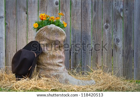 Blooming cowboy boot and a hat against wooden fence #118420513