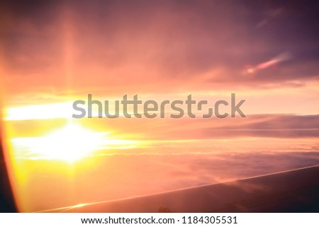 Beautiful sunset light over clouds view from airplane window  #1184305531