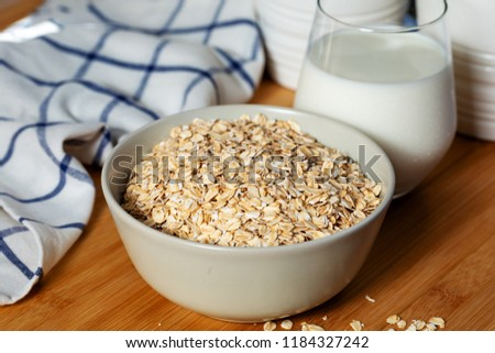 Bowl of oat flakes and glass of milk #1184327242