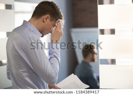 Nervous sweaty business man speaker preparing speech afraid of public speaking wiping wet forehead with handkerchief feeling stressed or worried about sweating before important office performance #1184389417