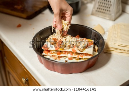 Woman cooking homemade classic lasagna bolognese, on dark blue table, with ingredients, top view copy space, hands in picture.