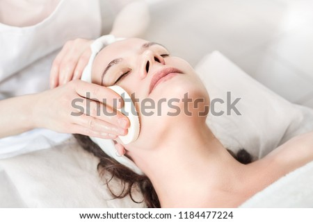 Hands of female beautician cleanses the skin. Facial skincare. Beautiful caucasian woman on a cosmetology procedure. Visit to the beauty salon #1184477224
