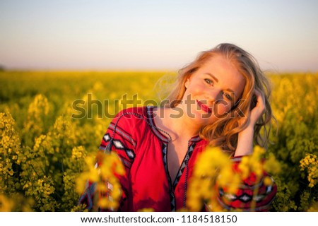 Portrait of a young beautiful woman on a flower field #1184518150