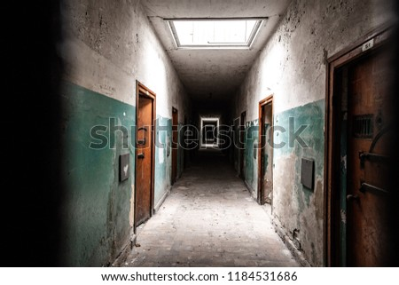 An old corridor of a creepy prison abandoned a long time ago.  Royalty-Free Stock Photo #1184531686