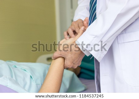 Physiotherapist is moving the patient's hand joints. To reduce the stiffness of the joints. #1184537245