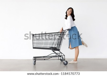 happy asian lady in shopping action with shopping cart on white background.   #1184570773