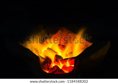 Fireplace with charcoal and flames.  #1184588302